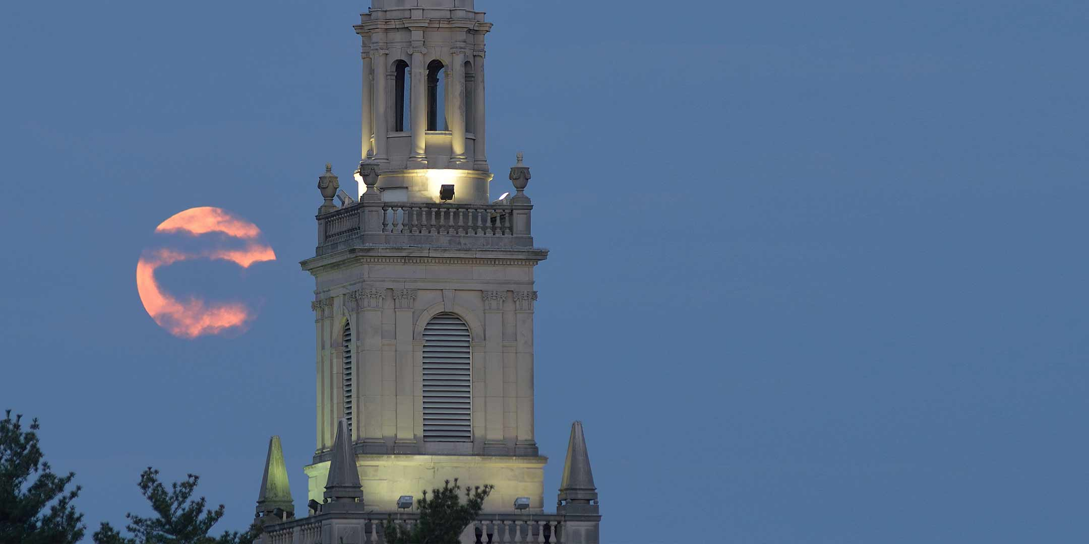 A full moon rising over Swasey Chapel